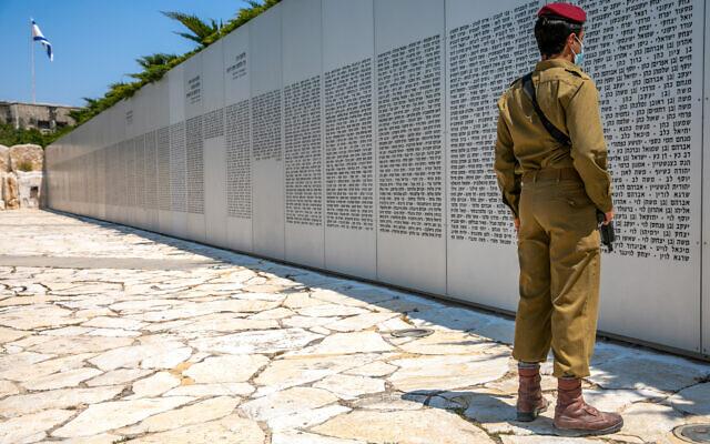 Un soldat israélien regarde le mur où sont inscrits les noms des soldats tombés du corps blindé dans le mémorial militaire de Latroun, le 13 avril 2021, en amont de Yom HaZikaron. (Crédit : Yossi Aloni / Flash90)
