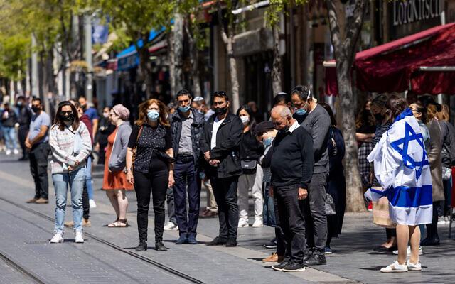 Des Israéliens restent immobiles alors qu'une sirène de deux minutes retentit à travers Israël, marquant Yom HaZikaron qui commémore les soldats israéliens tombés au combat et les victimes du terrorisme dans la rue Jaffa à Jérusalem, le 14 avril 2021. (Crédit : Nati Shohat / Flash90)