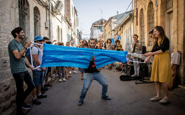 Un Israélien coupe un masque géant pour fêter la fin de l'obligation du port du masque à Jérusalem, le 18 avril 2021. (Crédit :  Yonatan Sindel/Flash90)