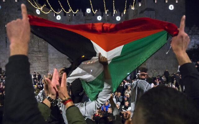 Des Palestiniens brandissent un drapeau palestinien à la porte de Damas, dans la Vieille Ville de Jérusalem, pendant le Ramadan, le 26 avril 2021. (Crédit : Olivier Fitoussi/Flash90)