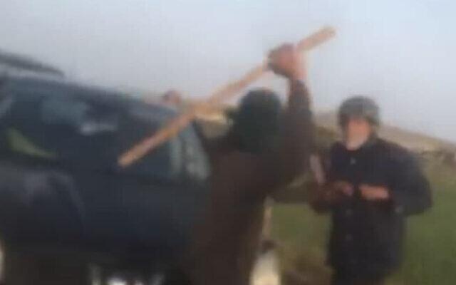 Un résjdent d'implantaiton frappe Arik Ascherman avec une batte en bois, le 7 avril 2021 en Cisjordanie, près de Ma'ale Ahuvia. (Capture d'écran : Gil Hammerschlag/ Twitter)