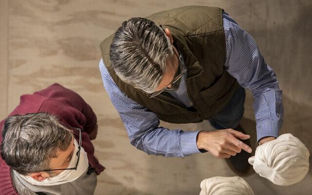 L'artiste Chas Fagan, (à droite), tient un modèle en argile du buste d'Elie Wiesel sous le regard du sculpteur sur pierre Sean Callahan, dans la cathédrale nationale de Washington, DC. Les deux hommes ont collaboré pour réaliser le buste, Fagan concevant le moule et Callahan le sculptant dans le mur de pierre. (Autorisation de la National Cathedral)