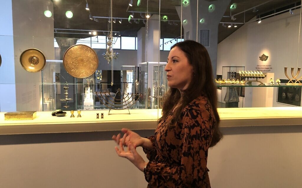 La conservatrice du musée d'Israël Sharon Weiser-Ferguson dans l'aile de l'Art et de la Vie juive, avec certains objets qui ont été donnés par les parents de Yadin Tanenbaum, mort pendant la guerre de Yom Kippour, en mémoire de leur fils. (Crédit : Jessica Steinberg/Times of Israel)