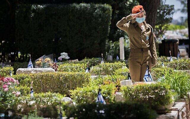 Une soldate israélienne place des fleurs sur les tombes des soldats israéliens tombés au combat au cimetière militaire du Mont Herzl, quelques heures avant le début du Yom HaZikaron, le 20 avril 2020. (Yonatan Sindel/Flash90)