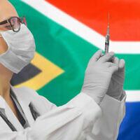 Une femme médecin avec une seringue devant un drapeau sud-africain. (Crédit :  Igor Vershinsky via iStock by Getty Images)