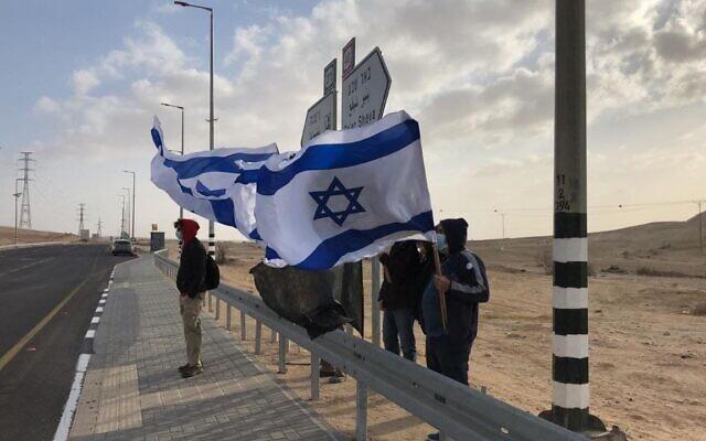 Des Israéliens manifestent contre le Premier ministre Benjamin Netanyahu à un carrefour situé aux abords de Tlalim, dans le sud d'Israël, le 10 avril 2021. (Autorisation : Drapeaux noirs)