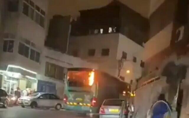Un bus Egged incendié dans le quartier d'Issawiya, à Jérusalem-Est, après avoir été pris pour cible par des émeutiers. 'Capture d'écran : Vidéo)