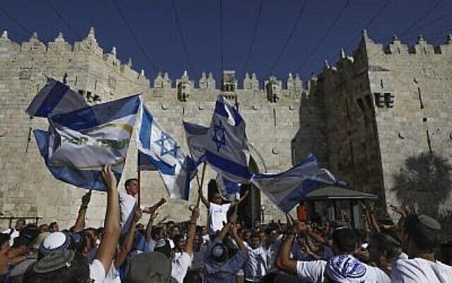 Des jeunes sionistes religieux brandissent des drapeaux israéliens alors qu'ils célèbrent Yom Yeroushalayim à la Porte de Damas de la Vieille Ville de Jérusalem, le 2 juin 2019. (Menahem Kahana/AFP)