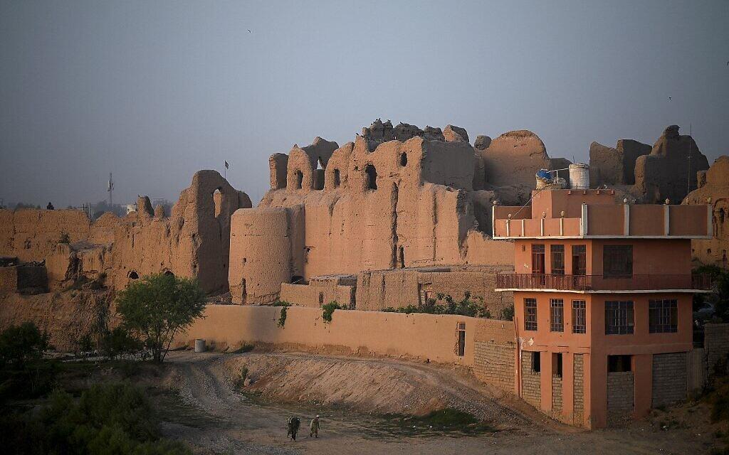 Sur cette photo prise le 27 mars 2021, des hommes marchent le long d'un sentier près d'un ancien palais où vivent des familles déplacées, au Qal-e-Kohna, un site historique de Lashkar Gah, la capitale de la province de Helmand. Autrefois résidence d'hiver des sultans d'illustres dynasties islamiques, les ruines d'une cité royale millénaire du sud de l'Afghanistan sont devenues le lieu de résidence de centaines de personnes qui ont fui les affrontements avec les talibans. (Crédit : WAKIL KOHSAR / AFP)