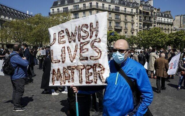 Un homme tient une pancarte alors que des personnes se rassemblent pour demander justice pour feu Sarah Halimi sur la place du Trocadéro à Paris, le 25 avril 2021. (Photo par GEOFFROY VAN DER HASSELT / AFP)