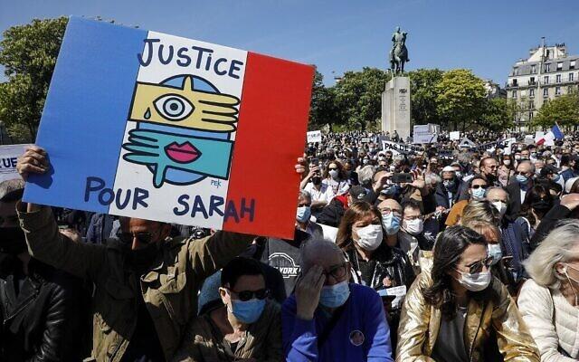 """Un homme tient une pancarte """"Justice pour Sarah"""" alors que des personnes se rassemblent pour demander justice pour la défunte Sarah Halimi sur la place du Trocadéro à Paris, le 25 avril 2021 (GEOFFROY VAN DER HASSELT / AFP)"""