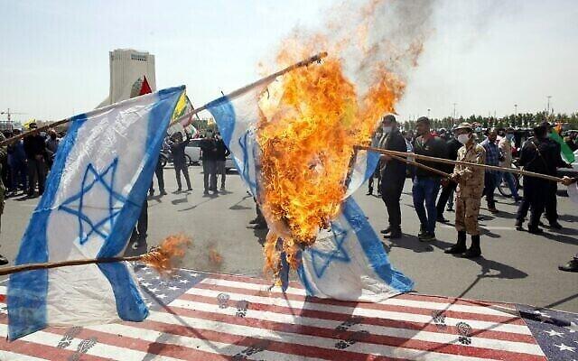 Les Iraniens mettent le feu à des drapeaux israéliens en piétinant des drapeaux américains pendant un rassemblement de la journée al-Quds dans la capitale de Téhéran, place Azadi (Liberté), le 7 mai 2021. (Crédit :  STR / AFP)