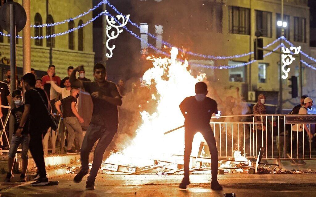 Des émeutiers palestiniens lancent des pierres sur les forces de sécurité israéliennes lors d'affrontements dans la Vieille Ville de Jérusalem, le 8 mai 2021. (EMMANUEL DUNAND / AFP)