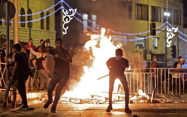 Des manifestants palestiniens lancent des pierres sur les forces de sécurité israéliennes lors d'affrontements dans la Vieille Ville de Jérusalem, le 8 mai 2021. (EMMANUEL DUNAND / AFP)