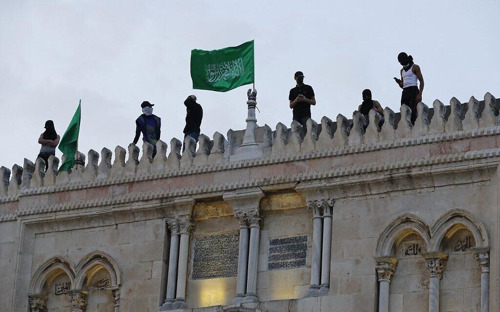 Des Palestiniens placent les drapeaux du Hamas au sommet de la mosquée al-Aqsa dans la vieille ville de Jérusalem, le 10 mai 2021, avant une marche prévue pour commémorer la prise de Jérusalem par Israël lors de la guerre des Six Jours en 1967. (Crédit : Ahmad GHARABLI / AFP)