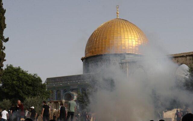Les forces de sécurité israéliennes lancent des gaz lacrymogènes pôur disperser des Palestiniens au sein du complexe de la mosquée al-Aqsa, à Jérusalem, le 10 mai 2021. (Crédit :  Ahmad GHARABLI / AFP)