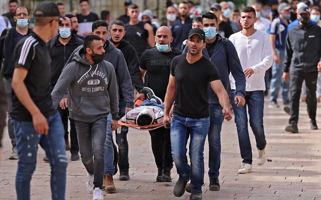Des Palestiniens évacuent un manifestant blessé lors d'affrontements avec les forces de sécurité israéliennes dans la vieille ville de Jérusalem, le 10 mai 2021, avant une marche prévue pour commémorer la prise de Jérusalem par Israël lors de la guerre des Six Jours en 1967. (Crédit : EMMANUEL DUNAND / AFP)
