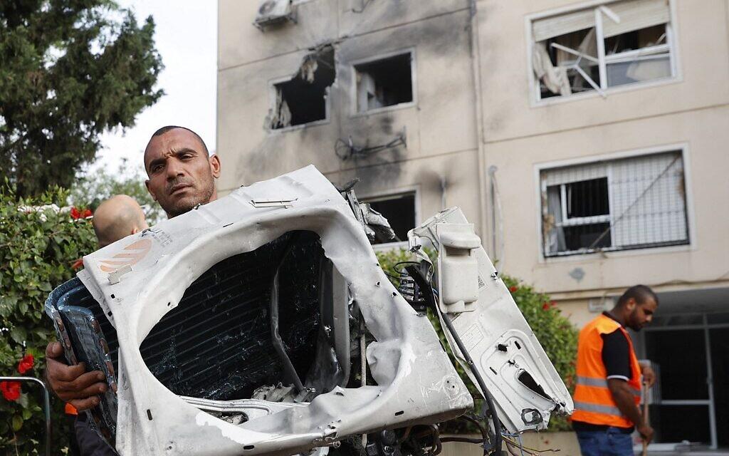 Un homme montre des morceaux d'une voiture touchée par une roquette lancée depuis Gaza à Ashkelon, le 11 mai 2021. (Crédit :  JACK GUEZ / AFP)