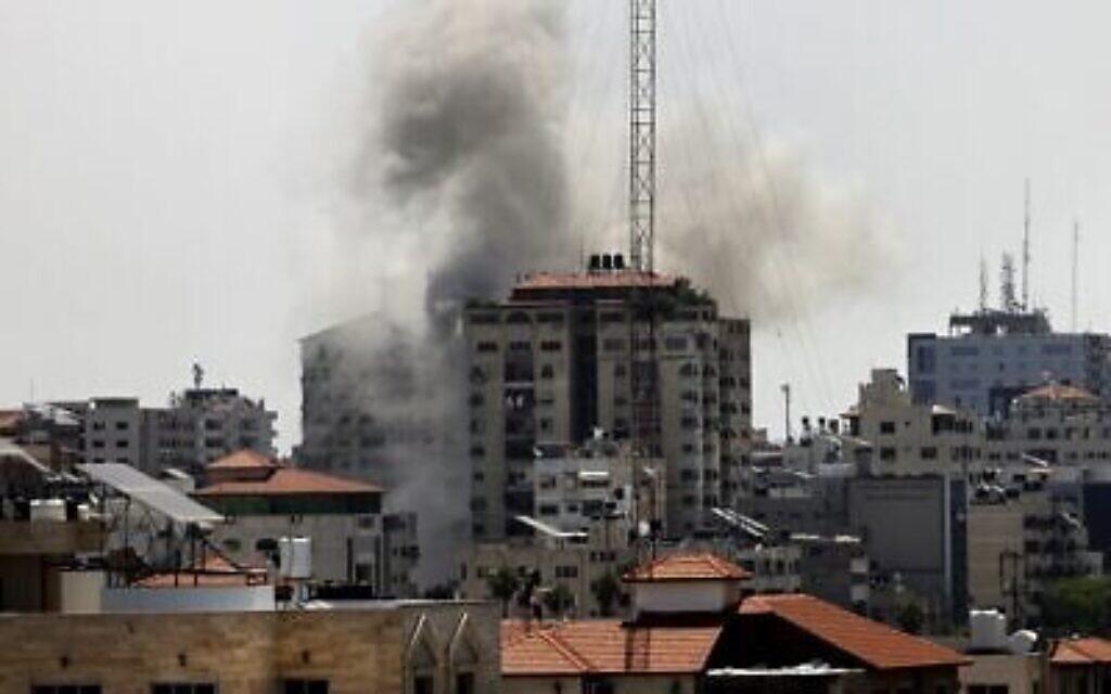 De la fumée s'élève d'un bâtiment frappé par les Israéliens à Gaza City, parmi les tirs de roquette de la bande, le 11 mai 2021. (Crédit : MOHAMMED ABED / AFP)