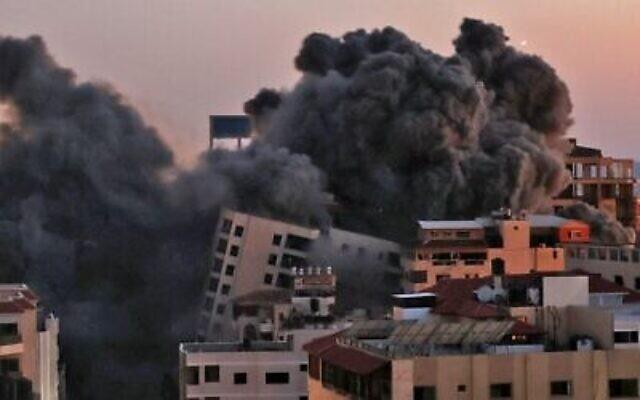 De la fumée s'élève après une frappe israélienne sur le complexe Hanadi à Gaza City, contrôlé par le groupe terroriste palestinien du Hamas, le 11 mai 2021. (Crédit : MOHAMMED ABED / AFP)