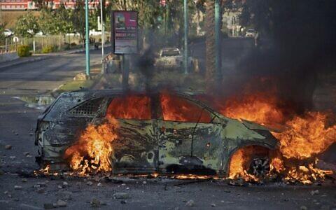 Une voiture de police israélienne en feu après une émeute d'Arabes israéliens à Lod, le 12 mai 2021. (Crédit : Ahmad GHARABLI / AFP)