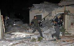 Des pompiers et des forces de sécurité israéliens inspectent les dégâts d'une maison touchée par une roquette tirée depuis Gaza, le 12 mai 2021 (Crédit : GIL COHEN-MAGEN / AFP)