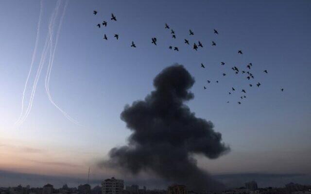 De la fumée s'élève après une série de frappes aériennes israéliennes dans la ville de Gaza, tôt le 12 mai 2021. (Crédit : MOHAMMED ABED / AFP)