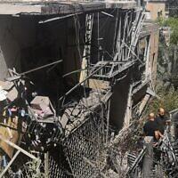 Des résidents israéliens inspectent une maison endommagée dans la banlieue de Tel Aviv, à Givatayim, le 12 mai 2021, après une frappe nocturne de roquettes, la première de l'histoire du quartier. (Crédit : Alexandra VARDI / AFP)