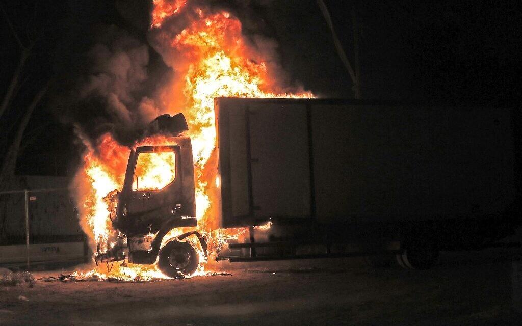 Un camion en feu après une émeute d'Arabes israéliens à Lod, le 12 mai 2021. (Crédit : Ahmad GHARABLI / AFP)