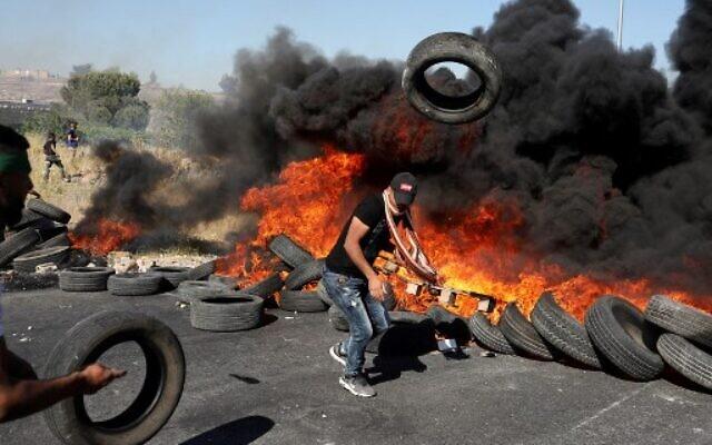 Un émeutier palestinien jette un pneu en feu sur un tas lors d'affrontements avec l'armée israélienne près de l'implantation juive de Beit El à proximité de Ramallah en Cisjordanie, le 14 mai 2021 (Crédit : ABBAS MOMANI / AFP)