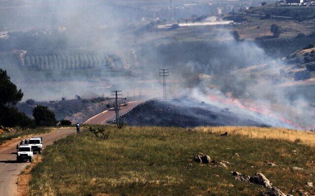 Les forces de maintien de la paix eu Liban regardent un feu déclenché lors d'un rassemblement propalestinien sur la frontière avec Israël, le 14 mai 2021. (Crédit : Mahmoud ZAYYAT / AFP)