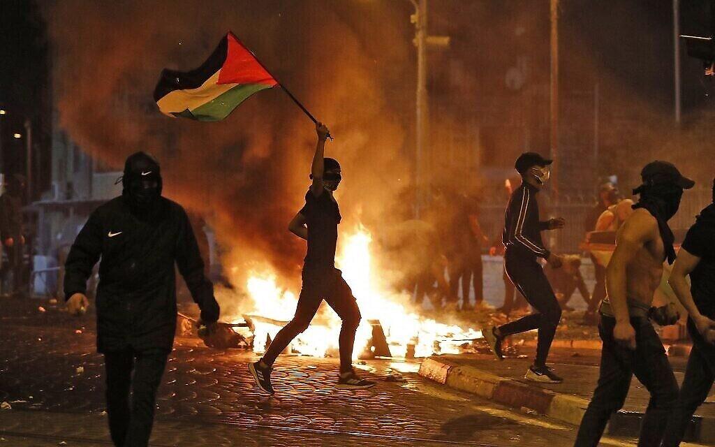 Des émeutiers palestiniens lancent des pierres lors d'affrontements avec les forces israéliennes dans le quartier palestinien de Shuafat à Jérusalem-Est le 14 mai 2021. (Crédit : Ahmad GHARABLI / AFP)