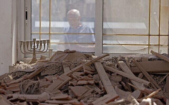 Un Israélien constate les dégâts causés à sa maison après une attaque à la roquette depuis la bande de Gaza, dans la ville de Sderot, le 15 mai 2021. (Crédit : JACK GUEZ / AFP)