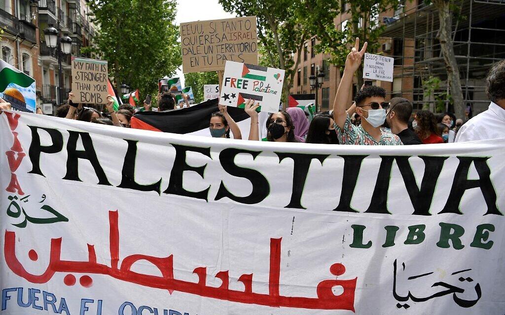 """Les gens tiennent un grand tissu où l'on peut lire en partie """"Palestina"""" alors qu'ils participent à une manifestation marquant le 73e anniversaire de la """"Naqba"""", à Madrid le 15 mai 2021. (Crédit : GABRIEL BOUYS / AFP)"""