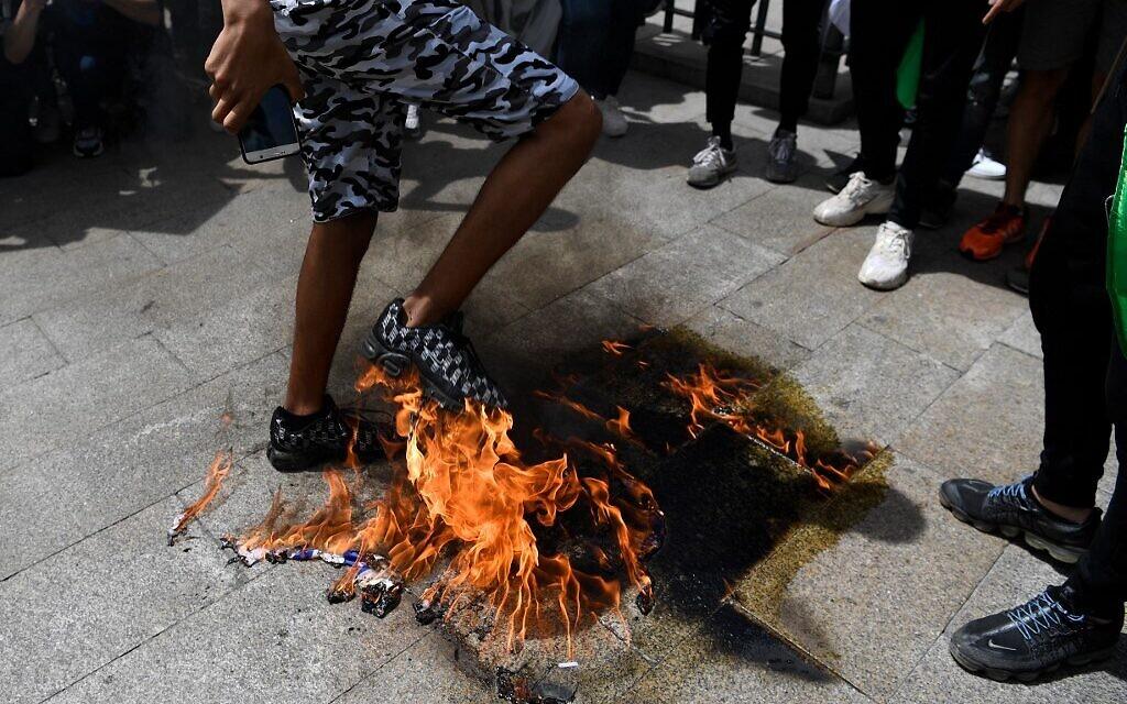 """Des manifestants brûlent un drapeau américain lors d'une manifestation marquant le 73e anniversaire de la """"Naqba"""" (catastrophe) à Madrid le 15 mai 2021. (Crédit : GABRIEL BOUYS / AFP)"""