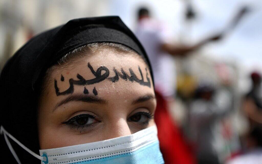 Une femme arbore le mot « Palestine » en arabe sur son front participe à une manifestation marquant le 73e anniversaire de la «Naqba» (catastrophe) à Madrid le 15 mai 2021. (Crédit : GABRIEL BOUYS / AFP)