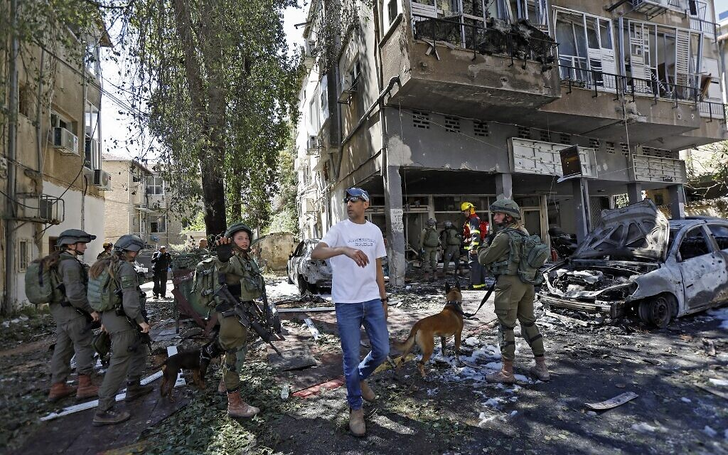 Des membres des services de sécurité et d'urgence israéliens travaillent sur un site touché par une roquette tirée depuis Gaza à Ramat Gan, où un Israélien a été tué, le 15 mai 2021. (Gil COHEN-MAGEN / AFP)