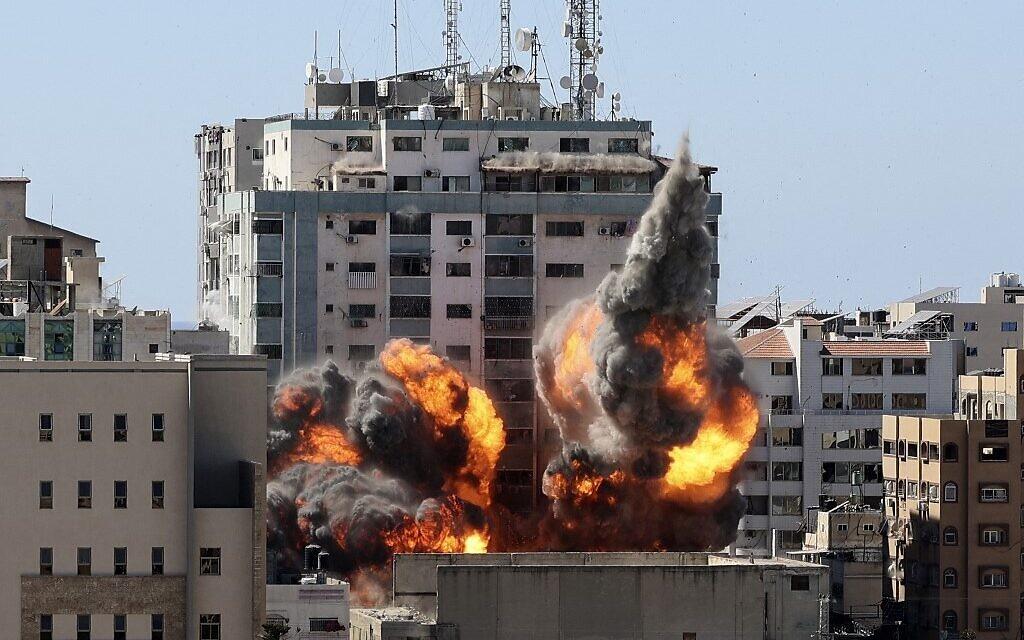 Le feu et la fumée montent de la tour Jalaa alors qu'elle est détruite lors d'une frappe aérienne israélienne après que Tsahal a averti les occupants de partir, à Gaza city, le 15 mai 2021 (Crédit : MAHMUD HAMS / AFP)