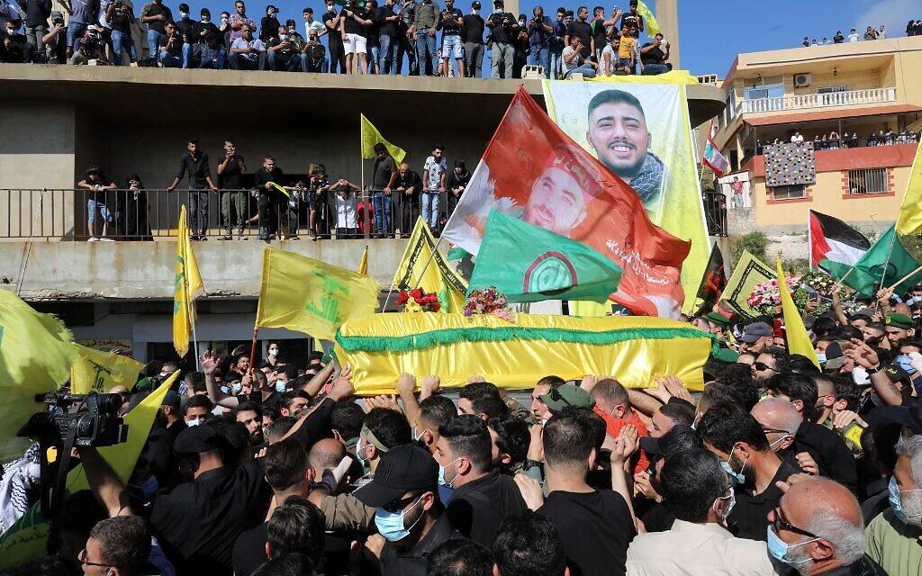 Des personnes en deuil portent le cercueil de Mohamad Kassem Tahan, membre du mouvement Hezbollah soutenu par l'Iran, tué un jour plus tôt à la frontière avec le Liban, lors de ses funérailles dans le sud du Liban village d'Adloun, le 15 mai 2021. - Des centaines de personnes brandissant des drapeaux palestiniens et les couleurs jaunes du Hezbollah se sont rassemblées pour les funérailles. (Crédit : Anwar AMRO / AFP)