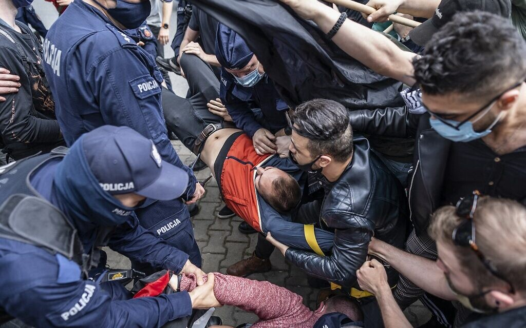 La police tente d'arrêter l'un des participants à une manifestation pro-Palestiniens appelés sur le conflit en cours avec Israël devant l'ambassade d'Israël à Varsovie, le 15 mai 2021 (Crédit : Wojtek RADWANSKI / AFP)