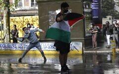 Un manifestant tient un drapeau palestinien devant des policiers français alors qu'un autre tire un projectile sur les forces de l'ordre, à Paris, le 15 mai 2021. (Crédit : GEOFFROY VAN DER HASSELT / AFP)