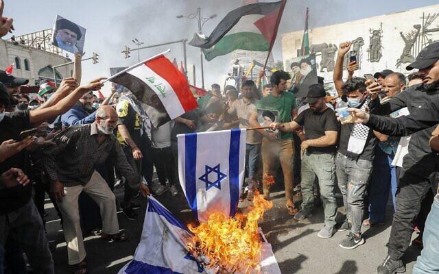 """Des Irakiens ont mis le feu à des drapeaux israéliens lors d'un rassemblement, dans la capitale Bagdad le 15 mai 2021, à l'occasion du 73e anniversaire de la Nakba, la """"catastrophe"""" que représente pour les Palestiniens, la création d'Israël en 1948. (Crédit : Ahmad AL-RUBAYE / AFP)"""