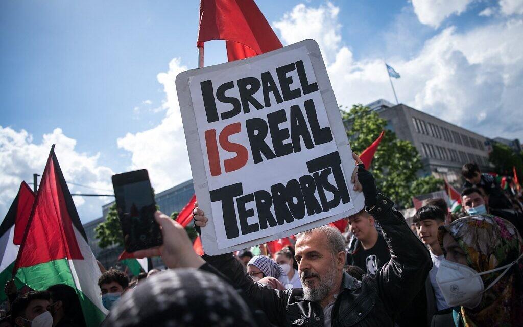 """Un manifestant tient une pancarte où l'on peut lire """"Israël est un vrai terroriste"""", le 15 mai 2021 sur la Hermannplatz à Berlin. (Crédit : STEFANIE LOOS / AFP)"""
