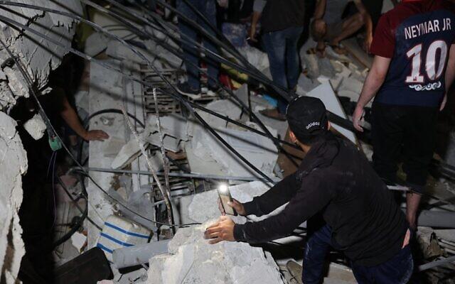 Des pompiers palestiniens cherchent des survivants et des corps sous les décombre après un intense bombardement à Gaza city suite à des tirs de roquette, le 16 mai 2021. (Crédit : MOHAMMED ABED / AFP)