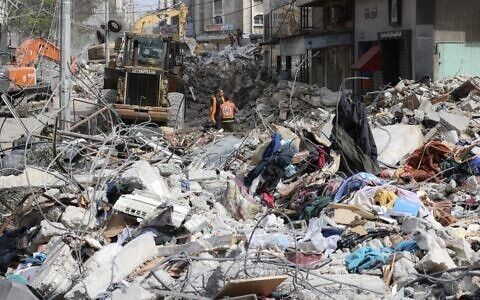 Une excavatrice nettoie les décombres d'un bâtiment détruit dans le quartier résidentiel chic de Rimal, à Gaza, le 16 mai 2021 (Crédit : Mahmud Hams / AFP)