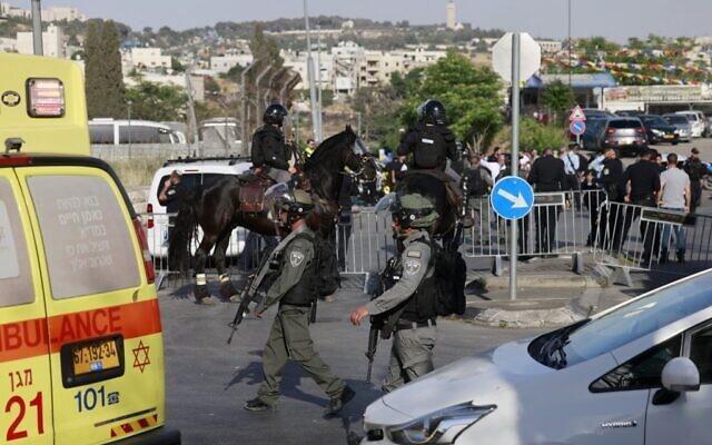 La police des frontières israélienne et la police montée sur les lieux d'une attaque à la voiture-bélier qui a fait plusieurs blessés à Jérusalem-Est, le 16 mai 2021. (Crédit : Menahem KAHANA / AFP)