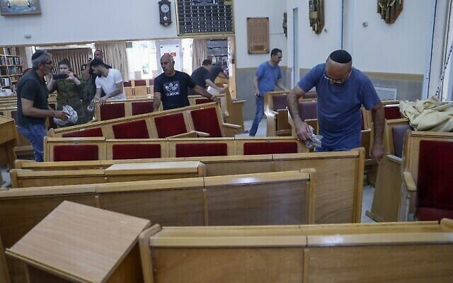 Des fidèles nettoient l'intérieur d'une synagogue endommagée suite à un tir de roquette de Gaza à Ashkelon, le 16 mai 2021. (Crédit : Jack Guez/AFP)