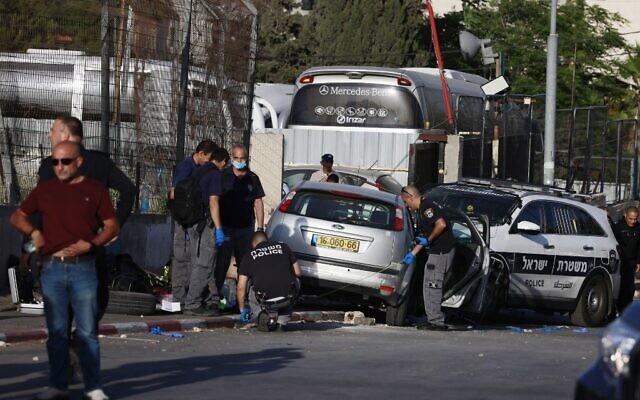 Les forces israéliennes de sécurité inspectent la scène d'un attentat à la voiture-bélier qui a blessé sept policiers dans le quartier sensible de Sheikh Jarrah, à Jérusalem-Est, le 16 mai 2021. (Crédit : Menahem KAHANA / AFP)