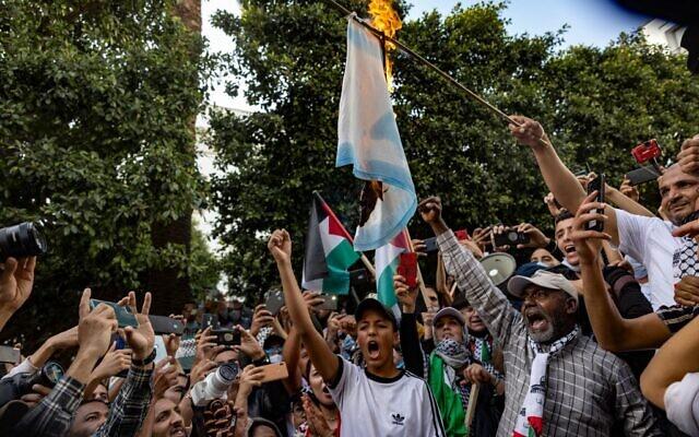 Les Marocains brûlent un drapeau israélien lors d'une manifestation contre la normalisation avec Israël, dans la capitale Rabat, le 16 mai 2021. (Crédit : FADEL SENNA / AFP)