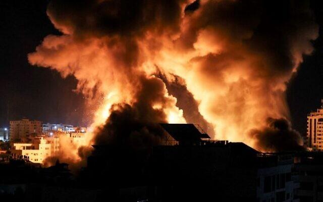 Des explosions éclairent la nuit au-dessus des immeubles de Gaza lors de frappes israéliennes sur l'enclave côtière, avant l'aube, le 18 mai 2021. (Crédit : MAHMUD HAMS / AFP) (Photo by Mahmud hams / AFP)
